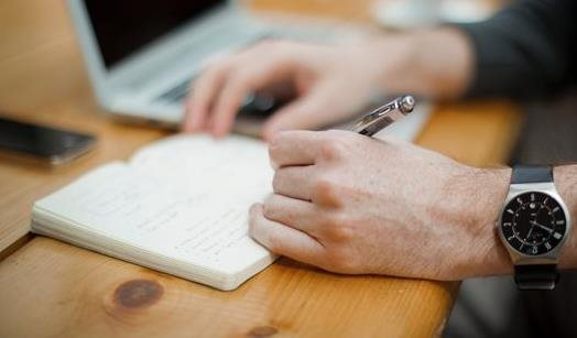A man writing in a notepad with a pen