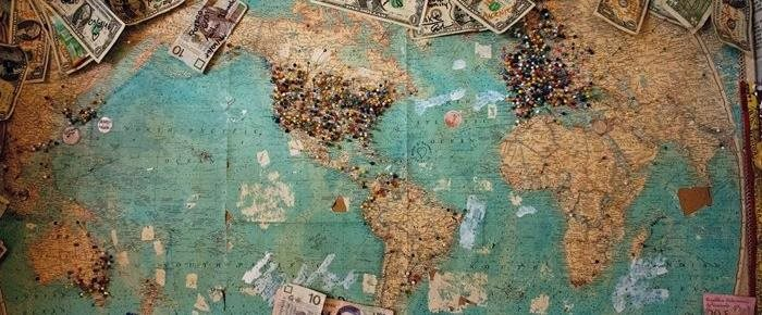 World map with money spread out on it